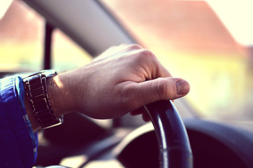 Driver hands holding steering wheel