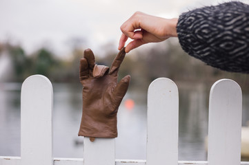 Hand picking up glove from a fence