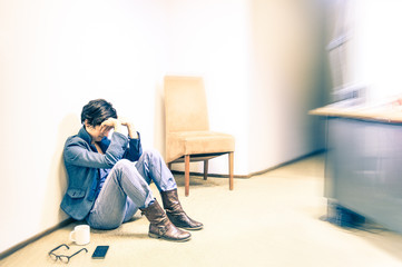 Depressed hipster business woman sit on the floor with headache