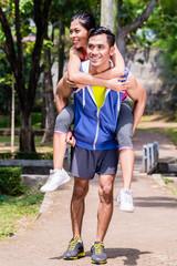 Asian man carrying his girlfriend piggyback for sport