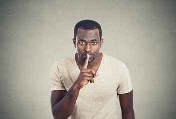 Man with finger on lips gesture keep quiet gray background