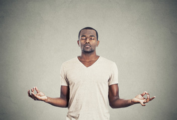 Young man meditating eyes closed on gray wall background