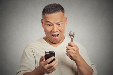 Excited man looking at smartphone holding wrench key instrument