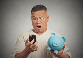 Shocked man looking at his smart phone holding piggy bank