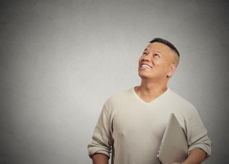 happy man with computer thinking looking up gray background