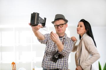 Man and woman hold retro camera