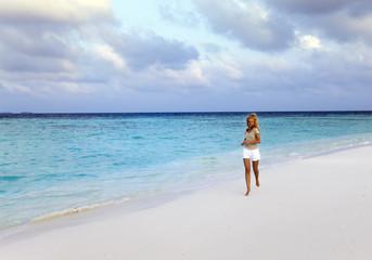 The woman runs on sea coast, Maldives