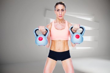 Serious female crossfitter lifting kettlebells