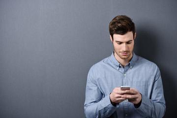 mann schaut auf sein mobiltelefon