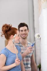glückliches junges paar streicht die wohnung