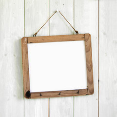 Blank message board hanging on retro white wooden wall
