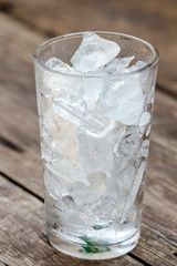 A glass of ice cubes on wooden