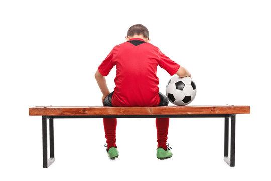 Rear view of a sad little boy in soccer jersey