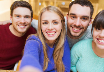group of smiling friends taking selfie