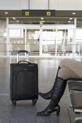 Woman waiting at the arrivals gate of an airport