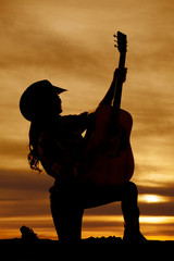 silhouette of a cowgirl with a guitar in hands kneeling