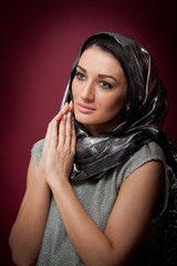Attractive brunette woman in gray blouse and headscarf posing