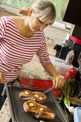 Attractive blond woman barbecuing meat