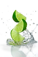 Three slices of lime falling into water