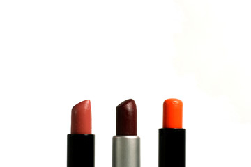 Three matte lipsticks, isolated on white background.