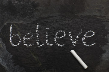 The word BELIEVE written with chalk on black stone