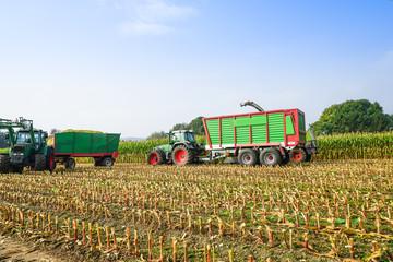 Wall Mural - Erntewagen mit Traktoren beim Mais häckseln