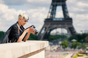 Happy young woman with camera in front of the Eiffel Tower. Pari