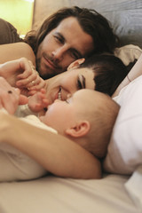 A mother, father and young baby playing at home.