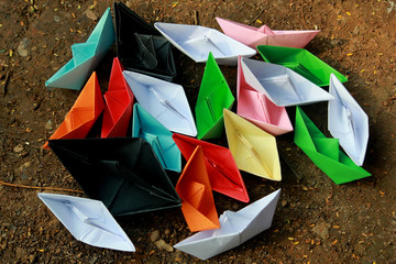 Colorful paper boats on barren land