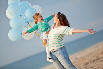 Mother with her daughter play with balloons by the sea