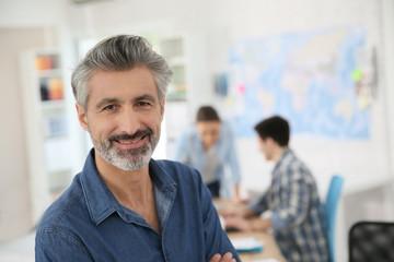 Portrait of mature teacher sitting in class