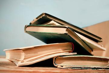 Old vintage books on wooden desk.