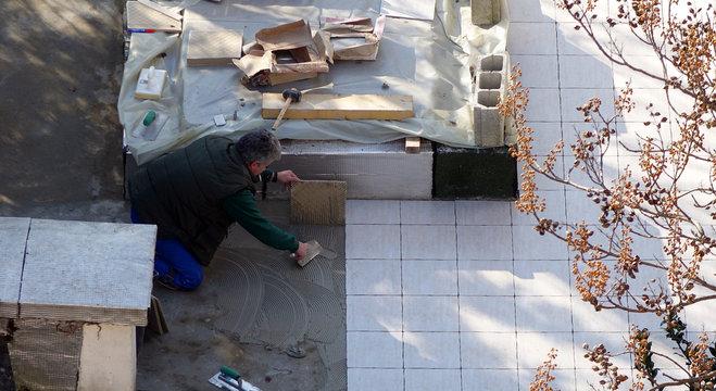 Un carreleur posant des dalles sur une terrasse