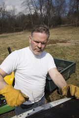 Man wearing work gloves taking shingles off roof