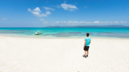 Man overlooking view of tropical white sand beach paradise lagoon full of healthy coral reef in Okinawa