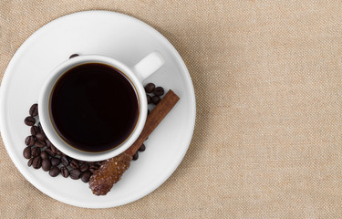 coffee cup with sugar on cinnamon stick, on the table covered