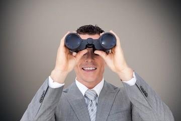 Composite image of businessman holding binoculars