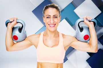 Happy female crossfitter lifting kettlebells