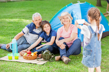 Girl Photographing Family At Campsite