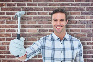 Composite image of happy handyman holding hammer