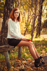 charming teen girl with red hair resting in the autumn park