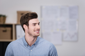 lächelnder geschäftsmann im büro schaut zur seite