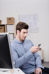 mitarbeiter im büro schaut auf sein mobiltelefon