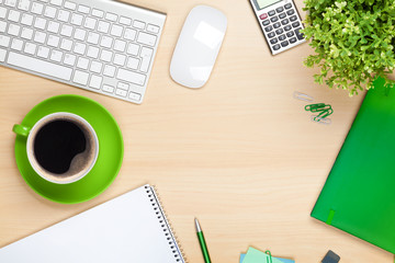 Office table with coffee cup, computer and flower