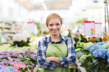 happy woman with flowers in greenhouse