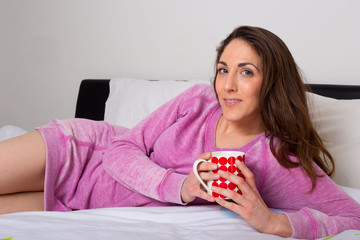young woman enjoying a hot drink in bed