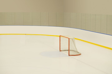 Empty hockey goal on ice rink.