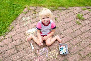 Little girl drawing with chalk at the backyard of the house