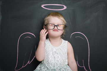 Little girl at the blackboard with wings and halo