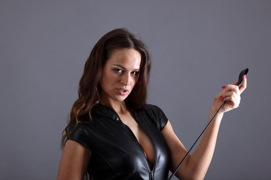 Domina with a whip in black